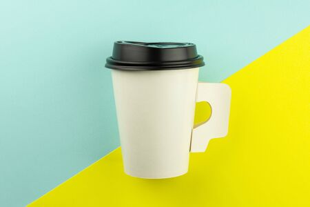 Take away paper coffee cup on blue and yellow background.