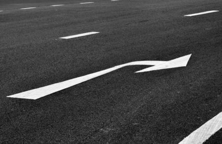 white arrow turn right sign on black asphalt. space transportation background Stock Photo
