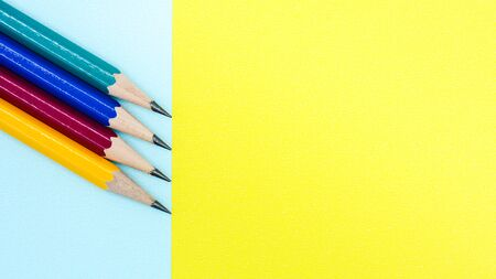 yellow, red, blue, and green pencil on blue and yellow paper - background 写真素材