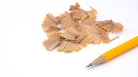 yellow pencil placed and the sharpener chips on white background Banco de Imagens