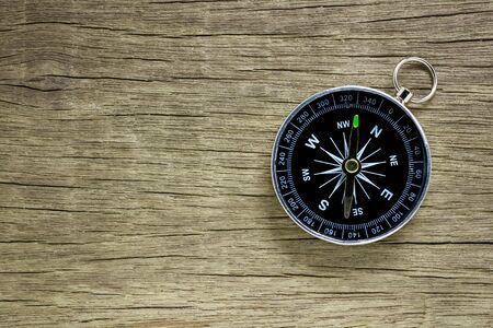 compass on old wood floor background.