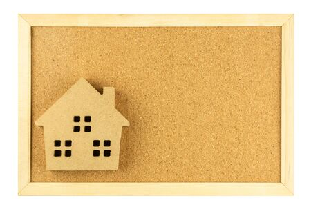 small model house on cork board in wooden frame isolated on white background. Stock Photo