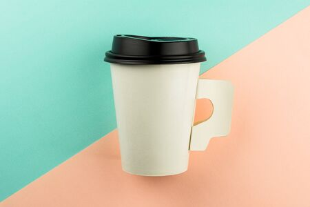 Takeaway paper coffee cup on blue and pink background.