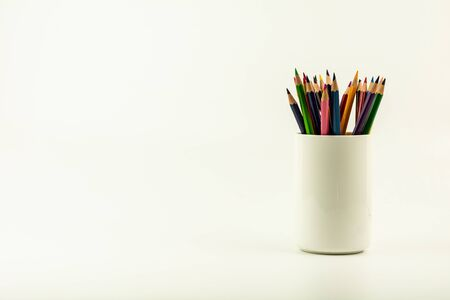 colorful of color pencils in white coffee cup.