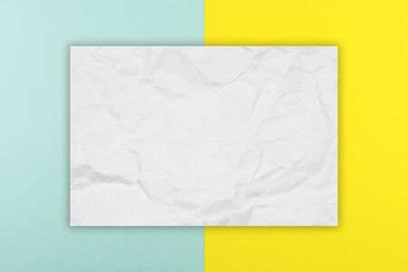crumpled white paper on blue and yellow paper background. - space for advertising message. Stock Photo