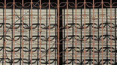 brown metal fence and the shadow