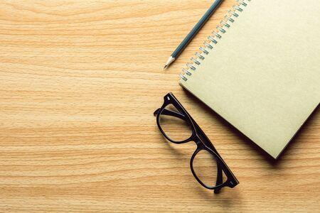 libro, matita e occhiali sulla scrivania in legno. - per lo sfondo del concetto creativo e aziendale. Archivio Fotografico