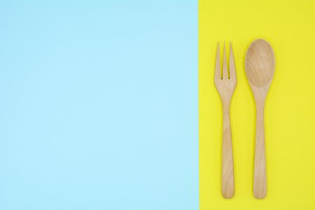 Wooden spoon and fork on blue and yellow paper background