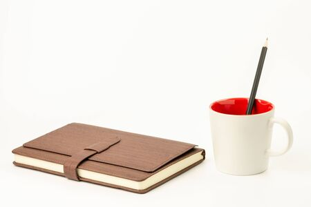 pencil in coffee cup and a leather book on white table.