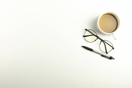 White office desk with glasses, pen and a coffee cup. - Top view with copy space.
