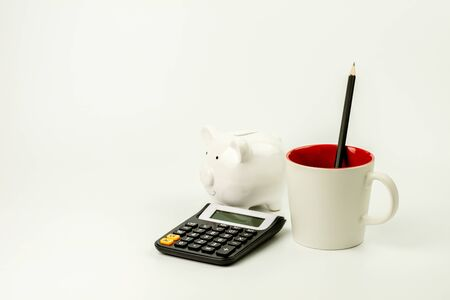 calculator, piggy bank and a office supplies on white table. - for creative and business concept background.