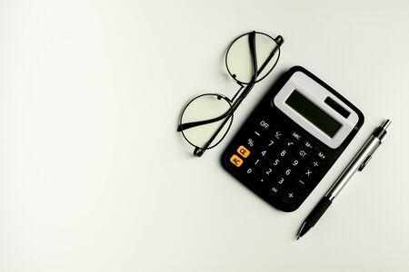 glasses, calculator and and a pen on white table. - top view with copy space.