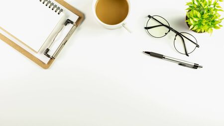 white office desk table with a coffee cup, pen, blank notebook and glasses. - top view with copy space. 版權商用圖片