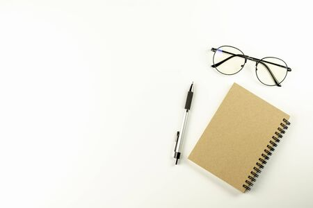 White office desk table with glasses, pen and a brown notebook. - Top view with copy space.