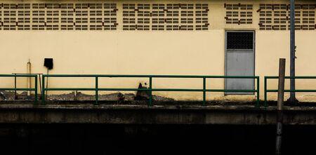 grey metal door at the old concrete building - background