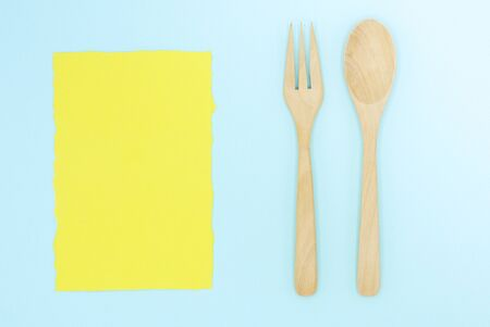 Wooden spoon and fork on blue paper background