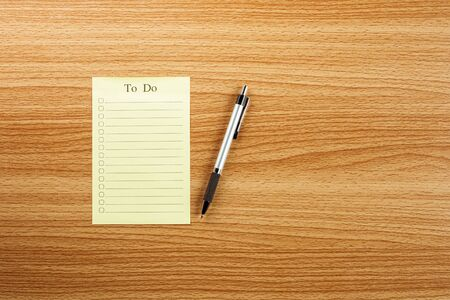 empty to do list and a pen on wooden desk.