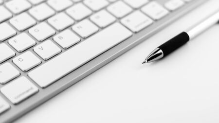 pen and keyboard on white desk background. Фото со стока