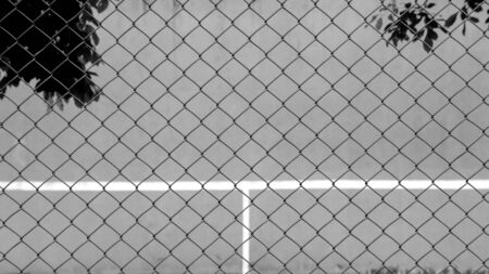 cage metal wire front the tennis court and wall for practice - monochrome