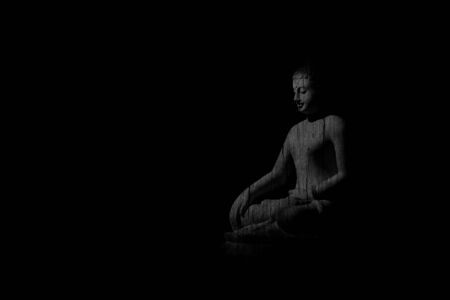 old wooden buddhist carving statue on black background. - vintage backdrop style.