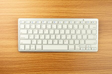 white computer keyboard on brown wooden desk.