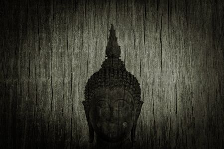 old buddhist statue on wooden background. - vintage backdrop style.
