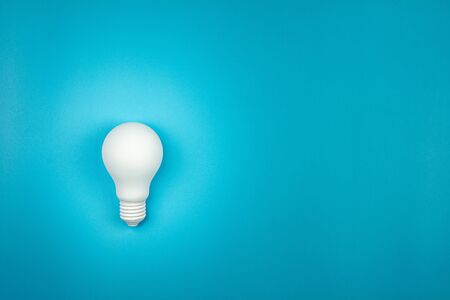 white light bulb is shine on blue table. - business growth and great ideas concept.
