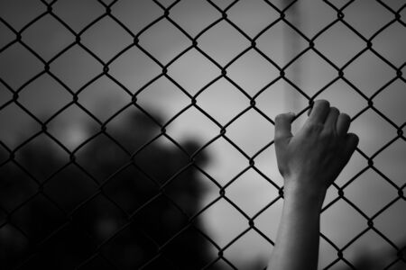 hand of women prisoner holding rustic metal fence.