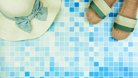 Sandals and a beach hat on blue ceramic tiles at the pool. - Summer holiday concept.