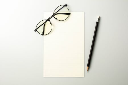 blank note paper and a pencil on grey desk background. Stock fotó