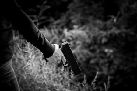 woman holding a gun in hand. - violence and crime concept.