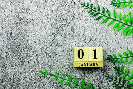 "vintage wooden calendar set at ""01 January"" on concrete floor."