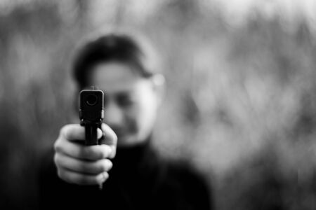 Woman pointing a gun at the target. - selective focus on front gun. Фото со стока