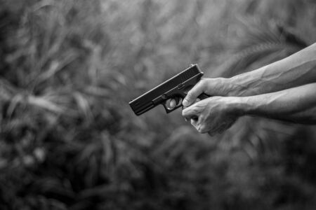 Man holding a gun in hand. - violence and crime concept.