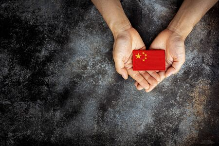 China flag in him hand. - Love, care, protect and safe concept.