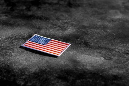 american flag on rusty abandoned metal floor in the dark.