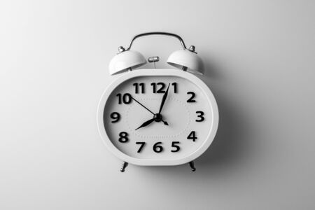 white alarm clock on white desk. - thinking and timing ideas concept.