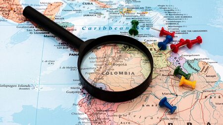 magnifying glass on the world map selective focus at Colombia map. - economic and business concept.