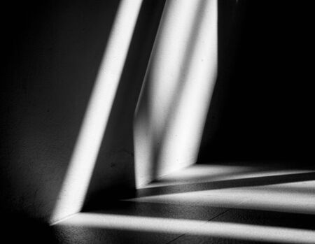 Abstract background of a white wall with shadows from the window. - monochrome Фото со стока