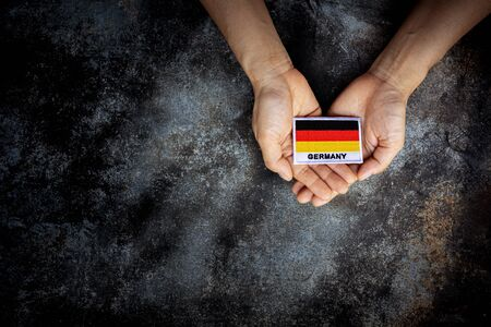 Small germany flag in a hand. - Love, care, protect and safe concept.
