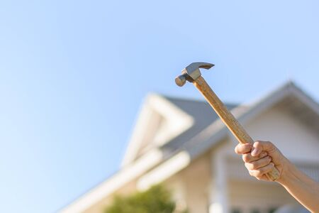 carpenter holding a hammer front the home for repairing. 版權商用圖片