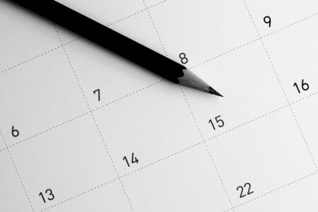 The pencil points to the 15 in the calendar. Фото со стока