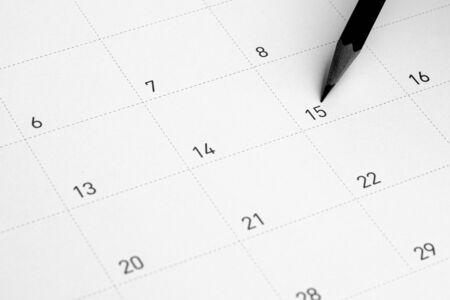 Le crayon pointe vers le 15 dans le calendrier.