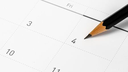 The pencil points to the 4 in the calendar. Фото со стока
