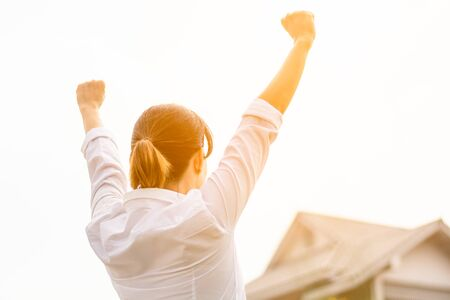 woman raise hands to show success front a home. - buy house and real estate concept.
