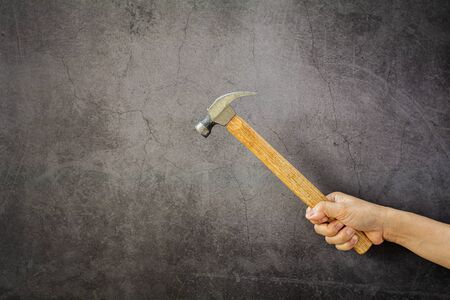 carpenter holding a hammer front the wall for repairing. Imagens