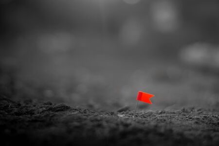 red push pin flag marking a location on the arid ground.
