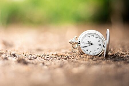 old pocket watch is discarded on the ground. - thinking and control timing ideas concept. Foto de archivo