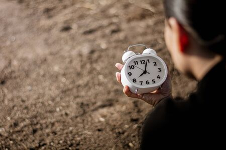 woman holding white alarm clock in a hand. - thinking and control timing ideas concept.
