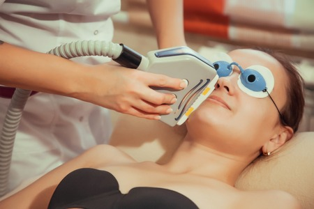 Young woman having mustache laser hair removal treatment in salon